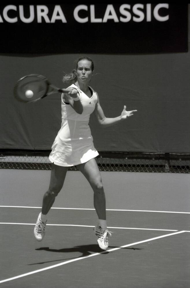 A person is swinging a racket at a ball  Description automatically generated